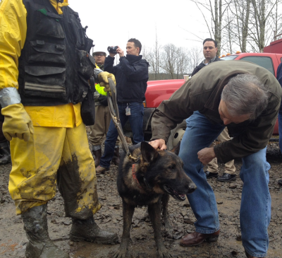 Governor Jay Inslee acknowledges a tired search dog with a scratch behind the ears.